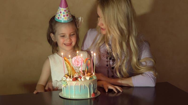 La madre e la figlia spengono le candele su una torta di compleanno e sulla fabbricazione del desiderio il compleanno di una bamb immagine stock