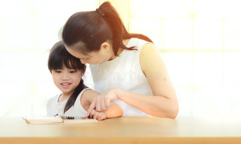 La madre e la figlia felici della famiglia hanno letto un libro a casa fotografia stock