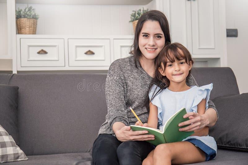 La madre e la figlia stanno imparando scrivere immagine stock