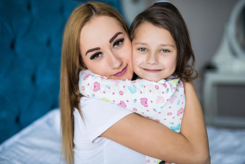 La madre e la piccola figlia godono di a letto a casa ed esaminando la macchina fotografica fotografia stock