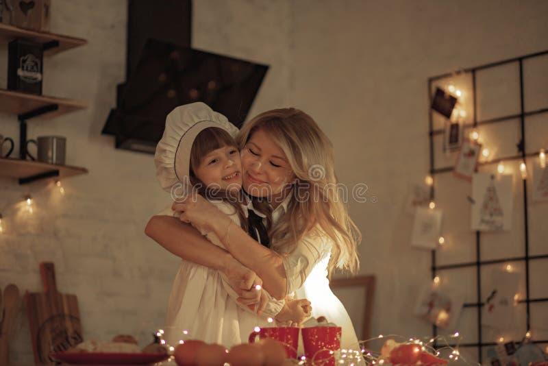 La madre e sua figlia macchiate da farina hanno un divertimento e un abbraccio fotografia stock