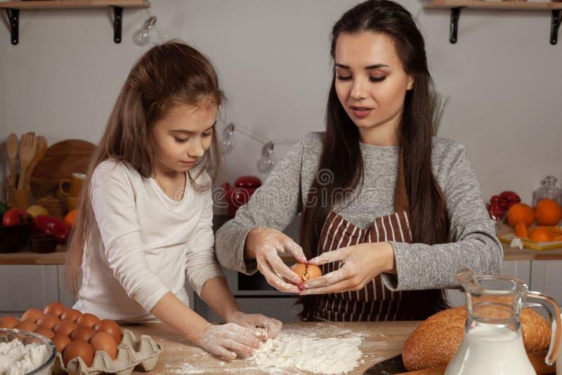 La madre e sua figlia stanno cocendo un pane e stanno divertendo alla cucina immagini stock libere da diritti