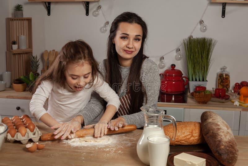 La madre e sua figlia stanno cocendo un pane e stanno divertendo alla cucina fotografie stock libere da diritti