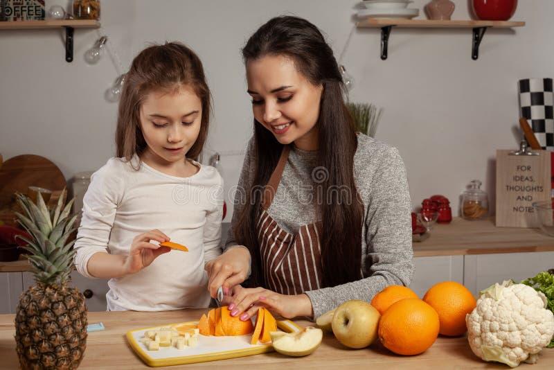 La madre e sua figlia stanno facendo un taglio della frutta e stanno divertendo alla cucina fotografie stock libere da diritti