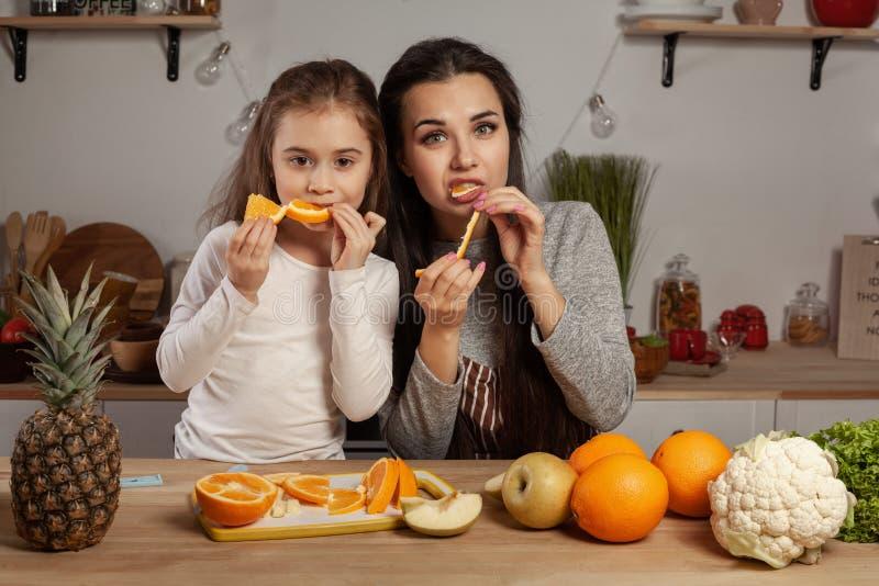 La madre e sua figlia stanno facendo un taglio della frutta e stanno divertendo alla cucina immagine stock