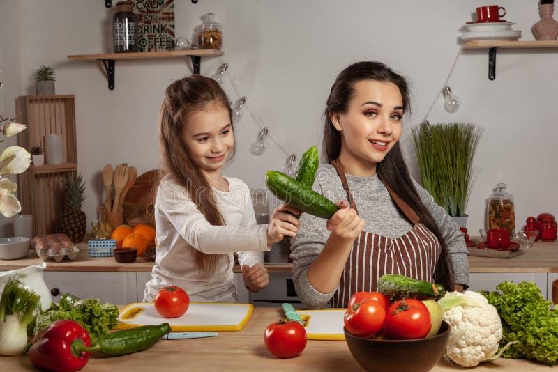 La madre e sua figlia stanno producendo un'insalata di verdure e stanno divertendo alla cucina fotografia stock