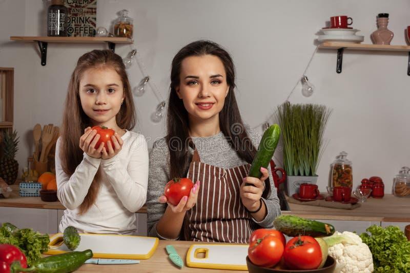 La madre e sua figlia stanno producendo un'insalata di verdure e stanno divertendo alla cucina immagine stock libera da diritti