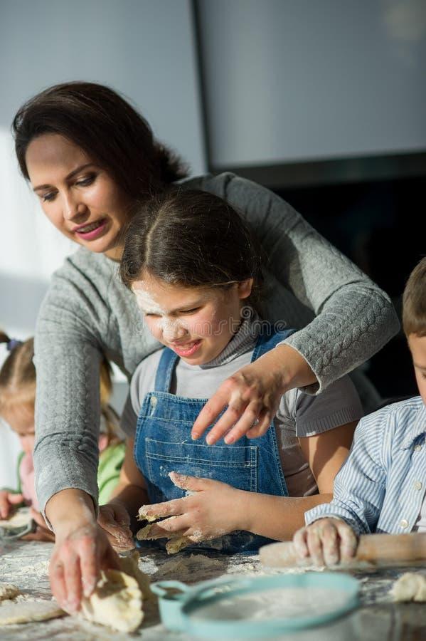 La madre e tre bambini preparano qualcosa dalla pasta fotografia stock libera da diritti
