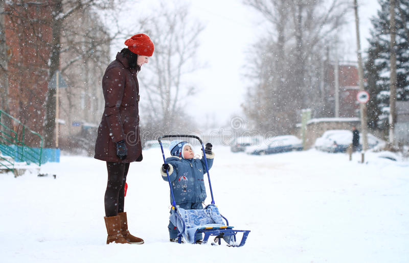 La madre ed il bambino camminano in inverno con le slitte fotografia stock