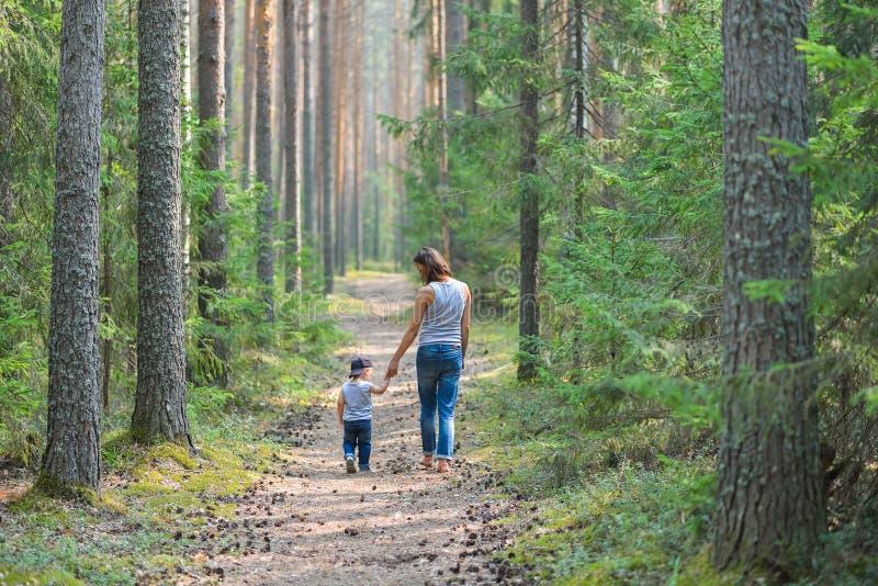La madre ed il bambino camminano sulla strada rurale del paese in abetaia fotografia stock