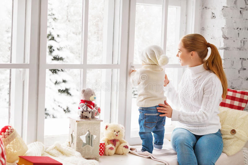 La madre ed il bambino felici della famiglia guardano fuori la finestra per l'inverno Chri immagini stock libere da diritti