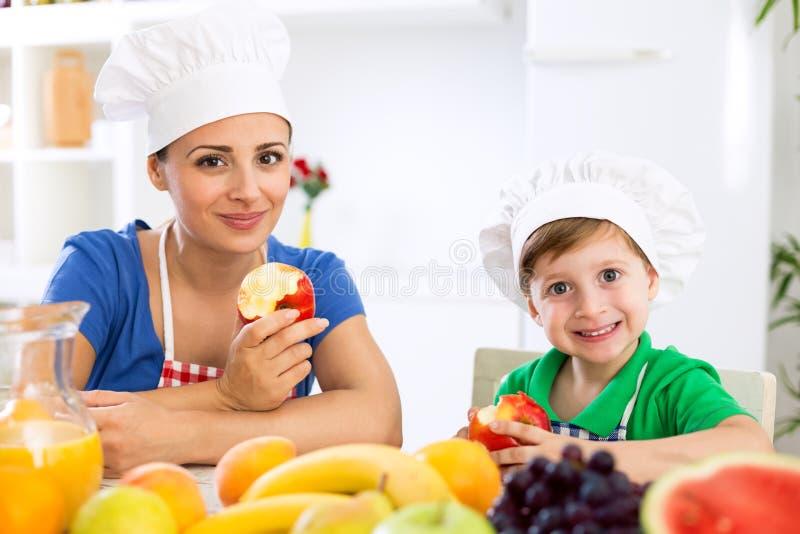 La madre ed il bambino felici sorridenti godono di e mangiare i frutti fotografia stock