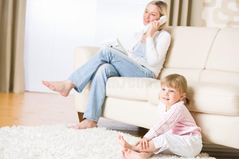 La madre ed il bambino in salone guardano la televisione immagini stock libere da diritti
