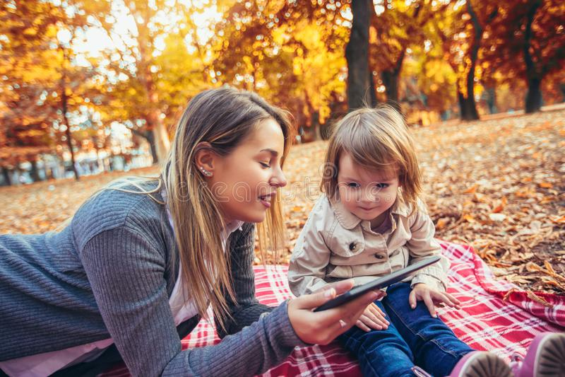 La madre ed il bambino sorridenti si siede insieme considerando il pc della compressa fotografie stock