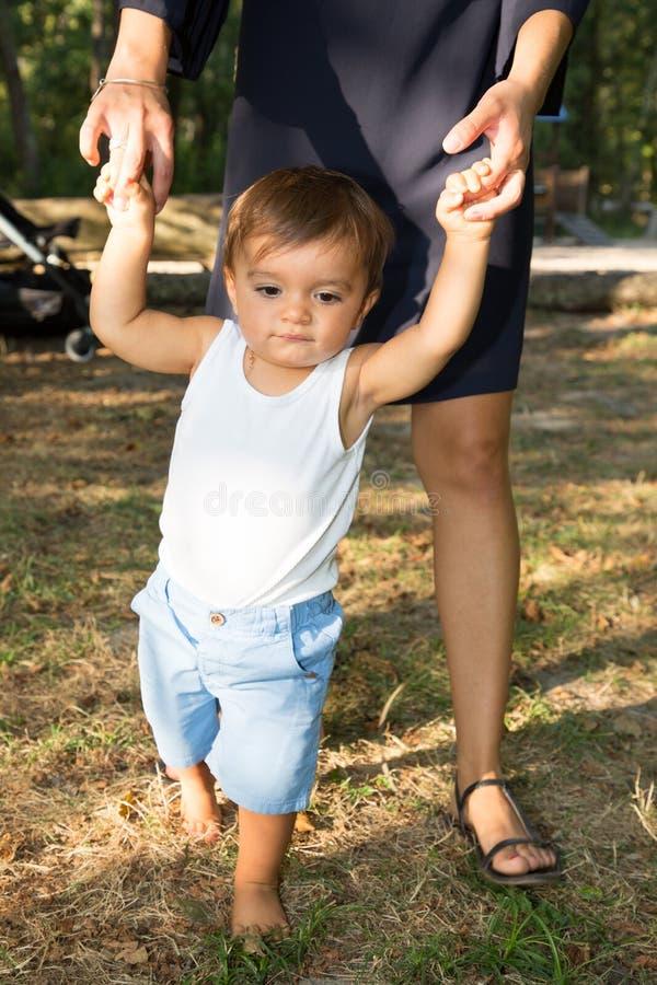 La madre ed il figlio del giardino che tengono congiuntamente imparano camminare fotografia stock
