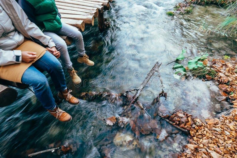 La madre ed il figlio si siedono sul ponte di legno sopra la torrente montano fotografia stock