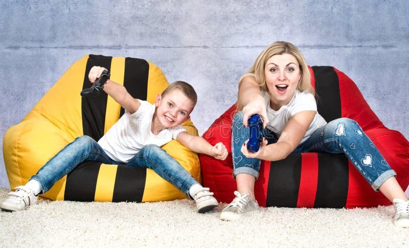 La madre ed il figlio si siedono sulle borse delle sedie e sui video giochi del gioco emozioni immagine stock