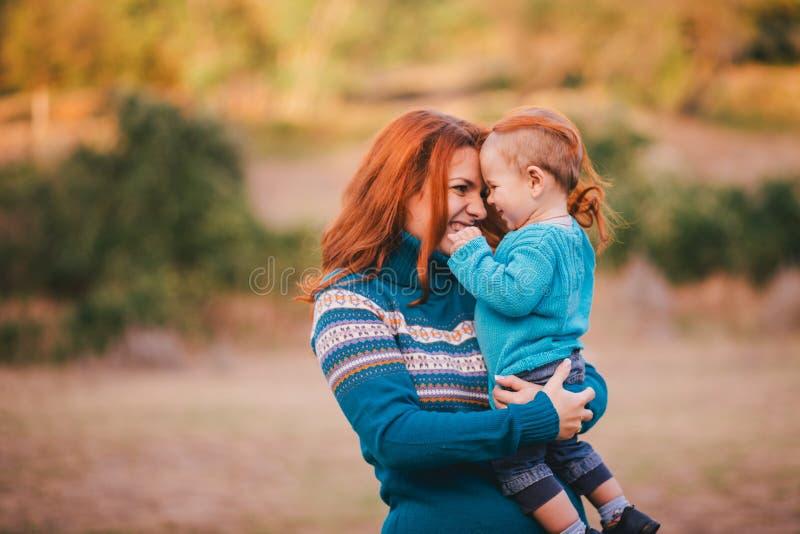La madre ed il suo piccolo figlio nei lavori o indumenti a maglia hanno una passeggiata in una foresta immagini stock libere da diritti
