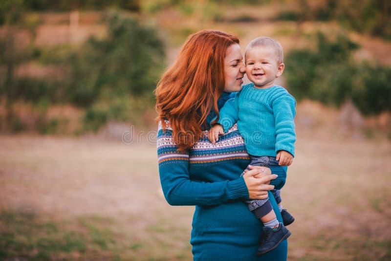 La madre ed il suo piccolo figlio nei lavori o indumenti a maglia hanno una passeggiata in una foresta fotografia stock
