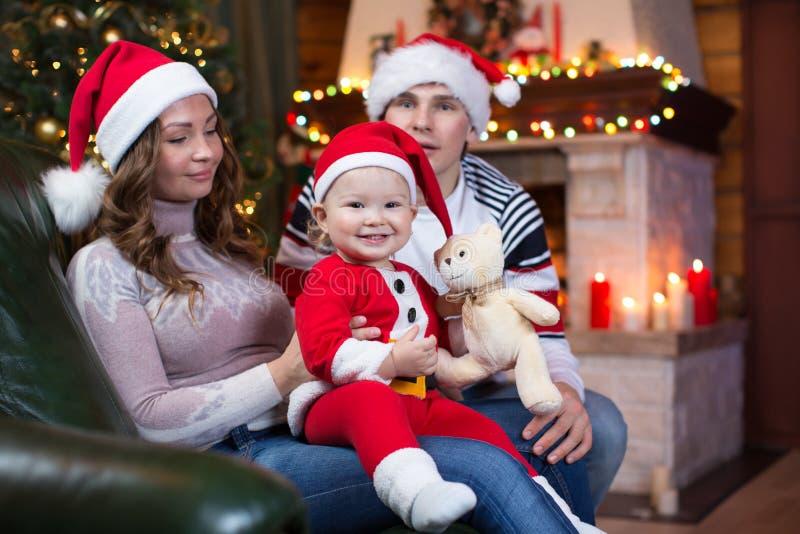 La madre, el padre y el bebé en el vestido rojo de santa sonríen en un fondo de árboles de navidad dentro de la casa foto de archivo