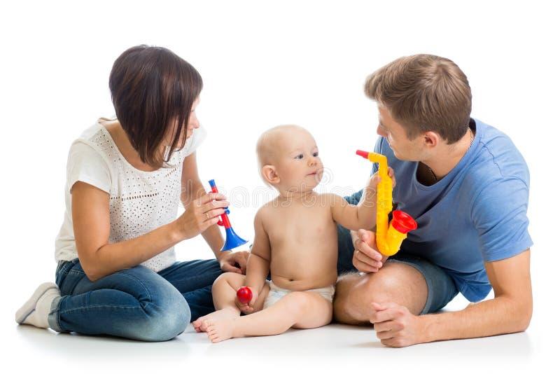 La madre, el padre y el bebé juegan los juguetes musicales Aislado en blanco imagen de archivo libre de regalías