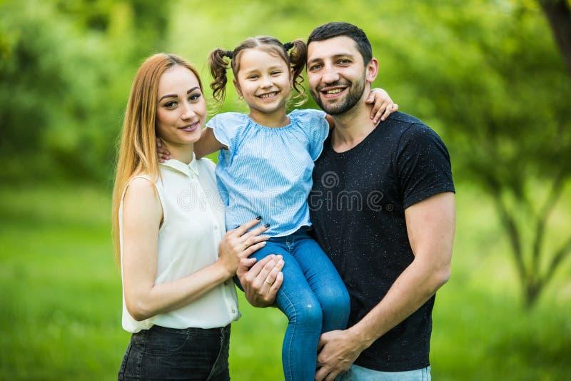 La madre, el padre y la hija jovenes felices en verano parquean imágenes de archivo libres de regalías