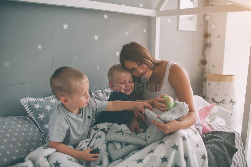 La madre embarazada y dos hijos están leyendo un libro interesante en casa por la mañana Forma de vida casual en dormitorio fotografía de archivo