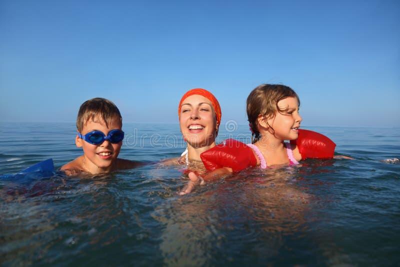 La madre en verano enseña para nadar el muchacho y a la muchacha fotos de archivo