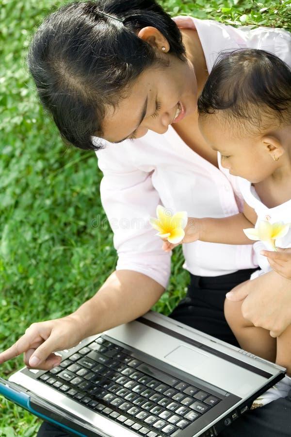 La madre enseña bebé a un conocimiento del ordenador fotos de archivo