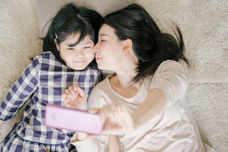 La madre es selfie con su pequeña hija que usa una cámara elegante del teléfono mientras que besa la mejilla de la hija fotografía de archivo libre de regalías