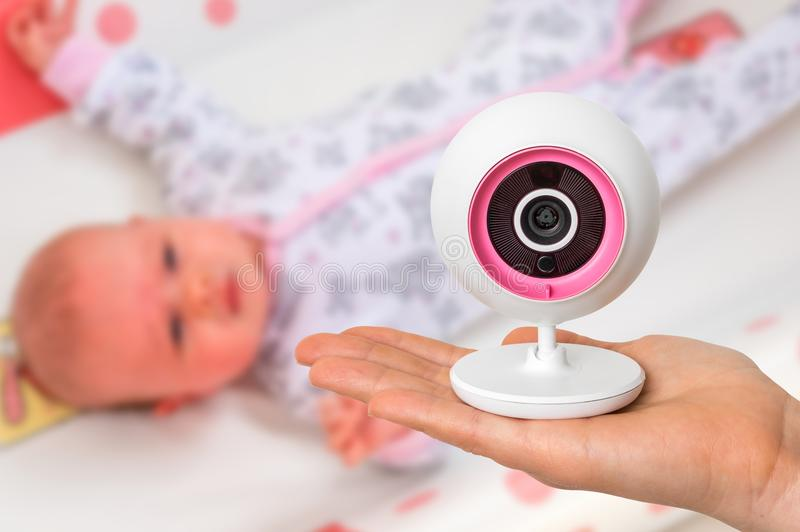 La madre está celebrando la cámara del monitor del bebé para la seguridad de su bebé fotografía de archivo libre de regalías