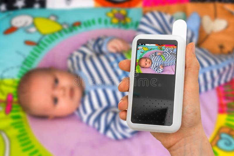La madre está celebrando la cámara del monitor del bebé para la seguridad de su bebé imagen de archivo libre de regalías