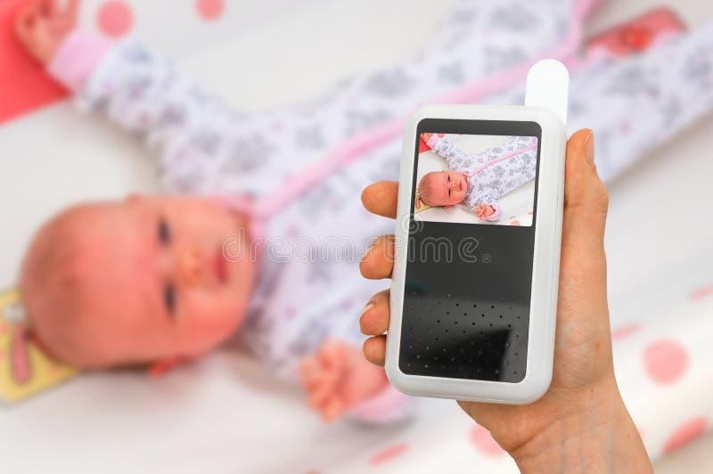 La madre está celebrando la cámara del monitor del bebé para la seguridad de su bebé imagen de archivo