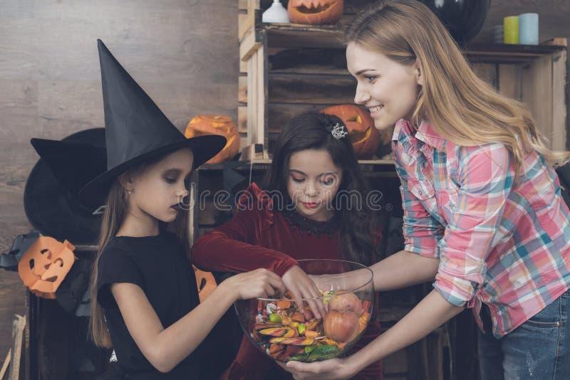 La madre está celebrando un florero con los dulces delante de los niños vestidos en trajes de los monstruos para Halloween imagen de archivo libre de regalías
