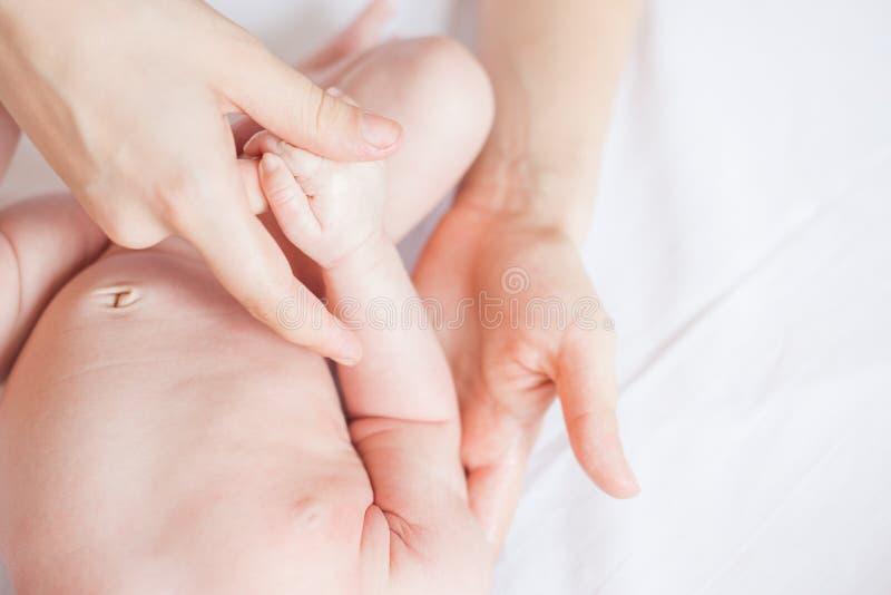 La madre fa il massaggio del bambino di professione d'infermiera fotografia stock