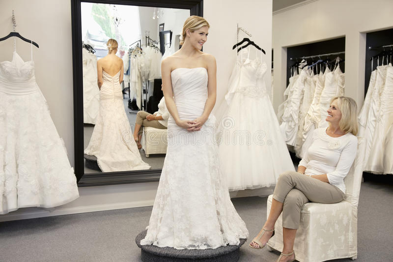 La madre felice che esamina la giovane figlia si è vestita in abito di nozze in boutique nuziale fotografia stock libera da diritti