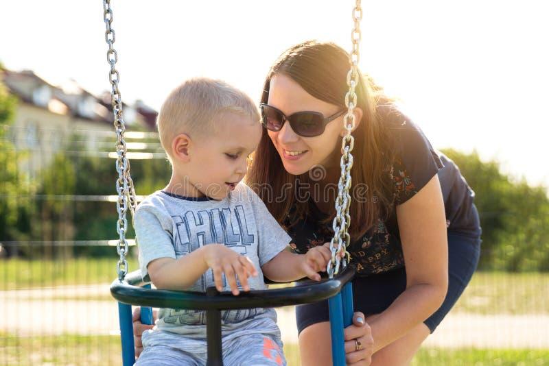 La madre felice con il bambino si siede sull'oscillazione immagine stock libera da diritti