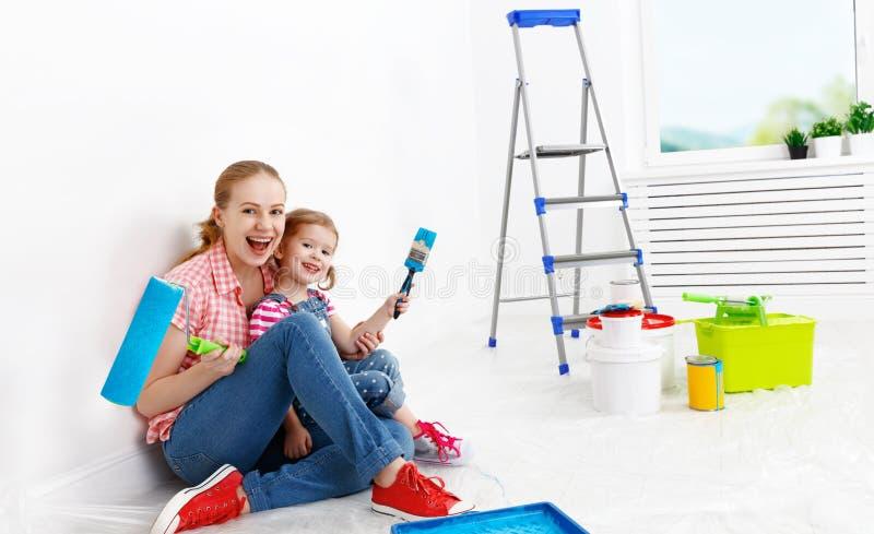 La madre felice della famiglia e la figlia del bambino che fa le riparazioni, dipingono wal immagini stock libere da diritti