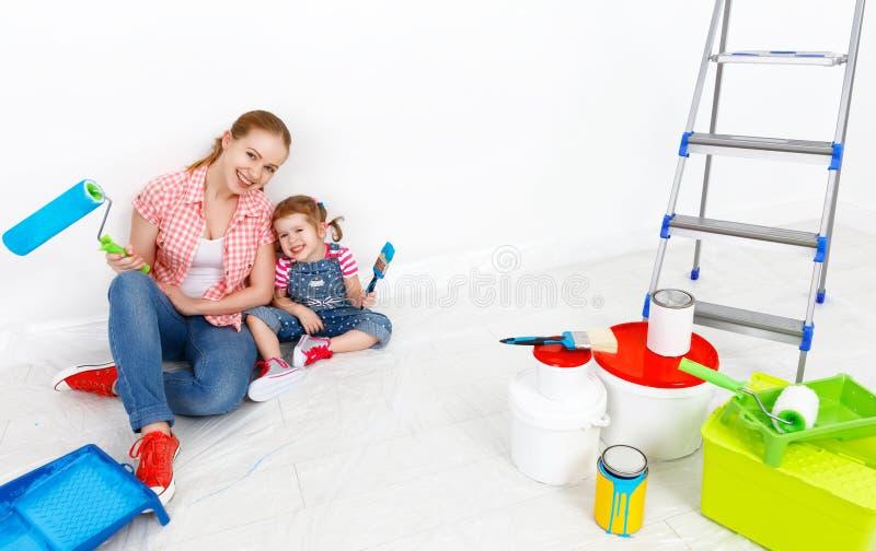 La madre felice della famiglia e la figlia del bambino che fa le riparazioni, dipingono wal fotografia stock