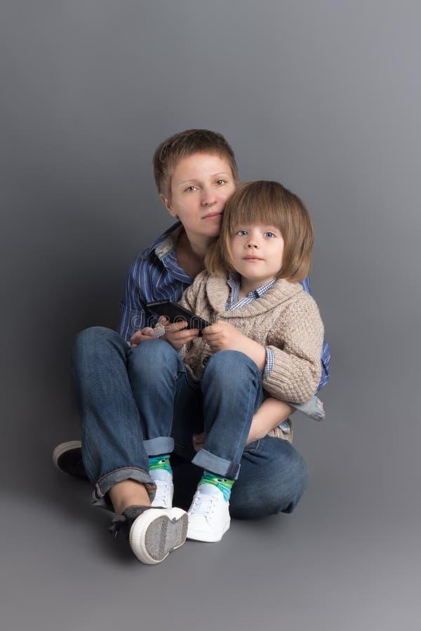 La madre felice ed i suoi 4 anni del piccolo figlio si sono vestiti in denim che si siede insieme sul fondo grigio per il tiro de immagine stock