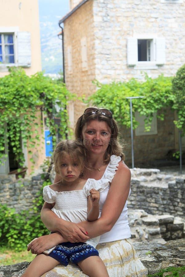la madre feliz abraza a la hija seria y la calma abajo fotos de archivo