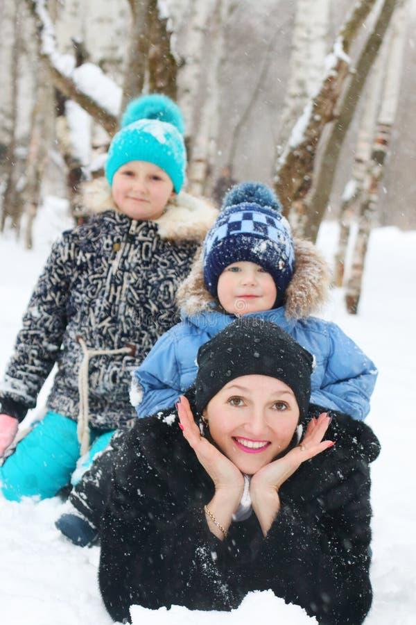 La madre feliz con dos niños miente en nieve durante las nevadas fotos de archivo