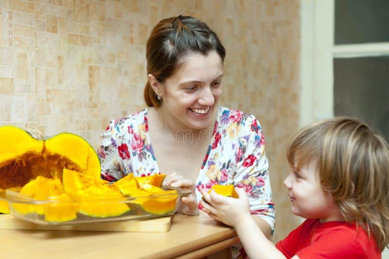 La madre feliz con la muchacha cocina la calabaza imagenes de archivo