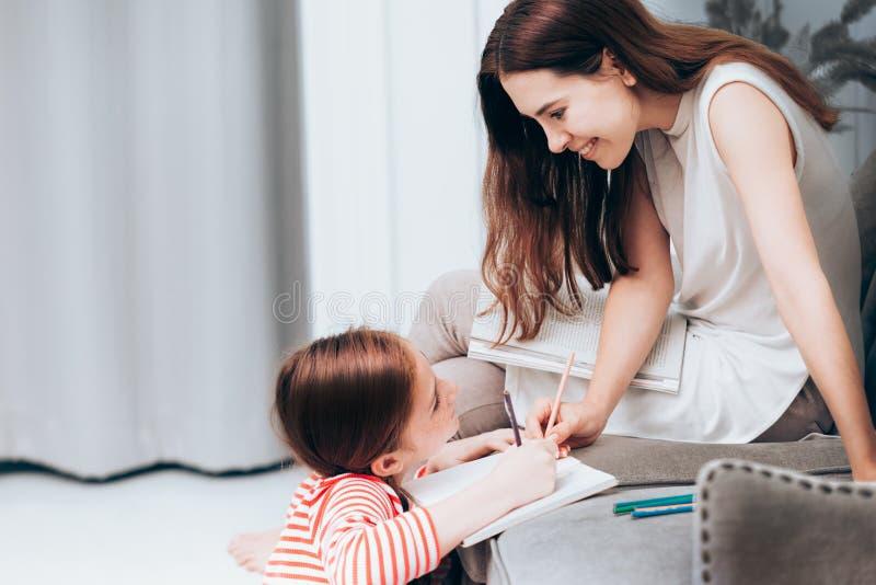 La madre feliz de la familia leyó un libro foto de archivo