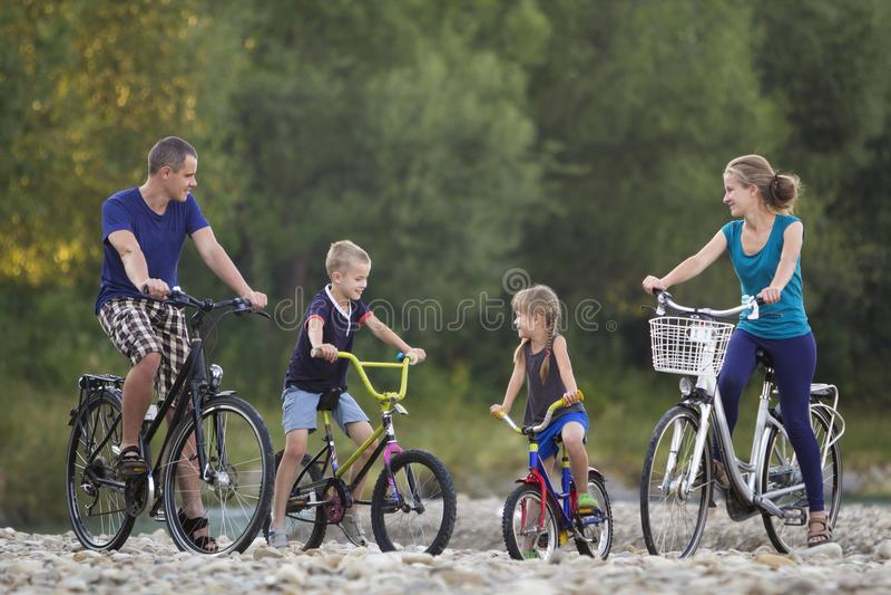 La madre feliz joven, el padre y dos montar a caballo rubios lindos de los niños, del muchacho y de la muchacha monta en biciclet foto de archivo