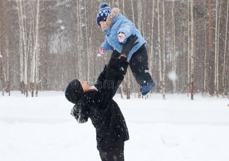 La madre feliz lanza para arriba a su hijo joven en parque imágenes de archivo libres de regalías
