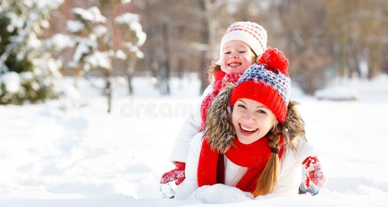 La madre feliz y el niño de la familia que juegan el invierno caminan imagen de archivo libre de regalías