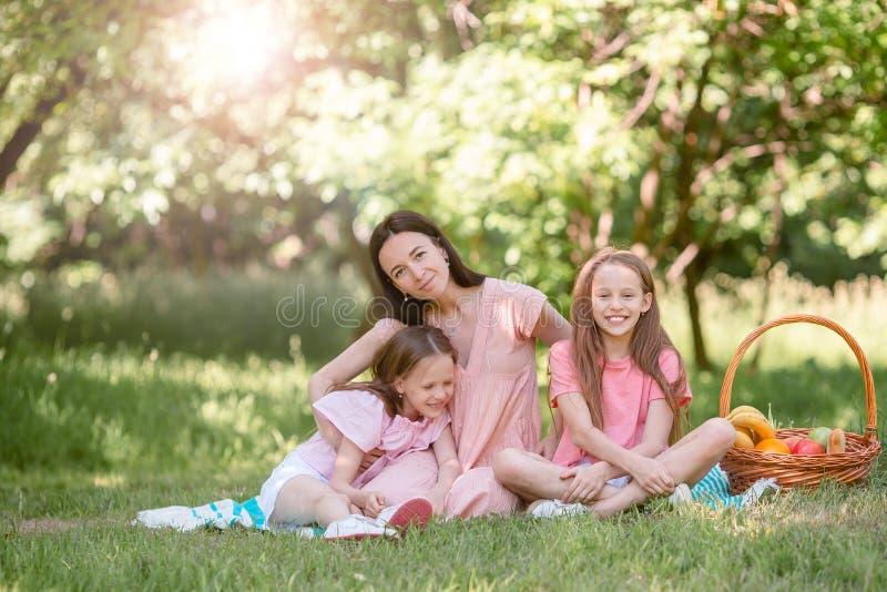 La madre feliz y los pequeños daughers se relajan por el lago imágenes de archivo libres de regalías
