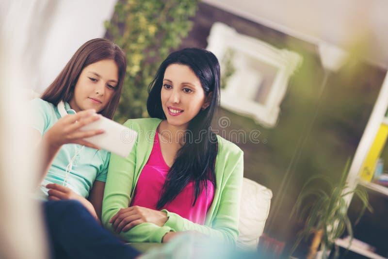 La madre feliz y su hija adolescente linda están mirando el teléfono móvil fotografía de archivo libre de regalías