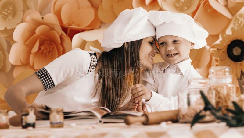 La madre feliz y su ni?o bajo la forma de cocineros preparan un festiv imagen de archivo libre de regalías